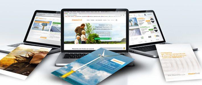 Bureau met 3 computers met websites en brochures