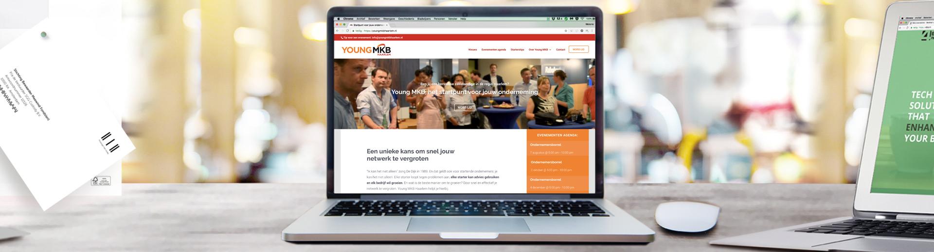 Bureau met laptop met daarom de nieuwe website van Young MKB