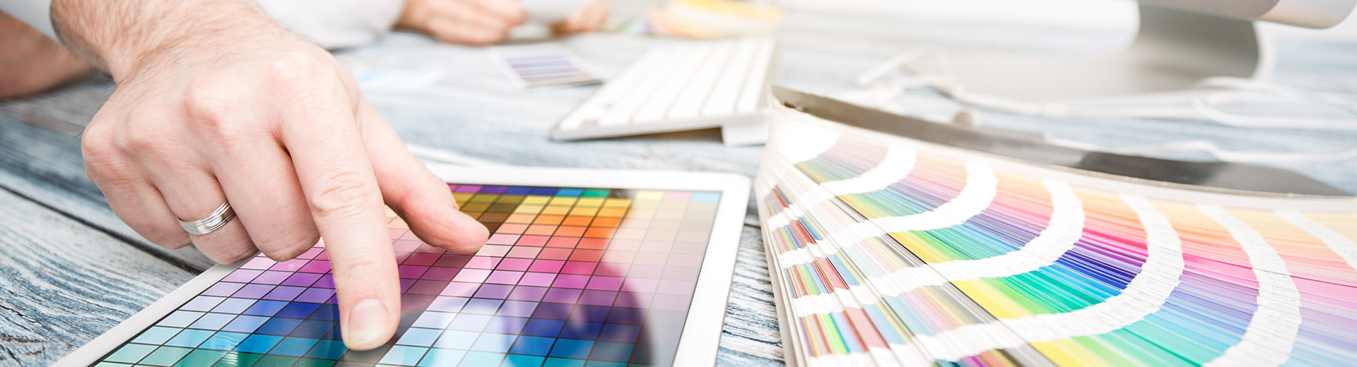 Bureau met mensen die werken aan corporate design met computer en kleurwaaier